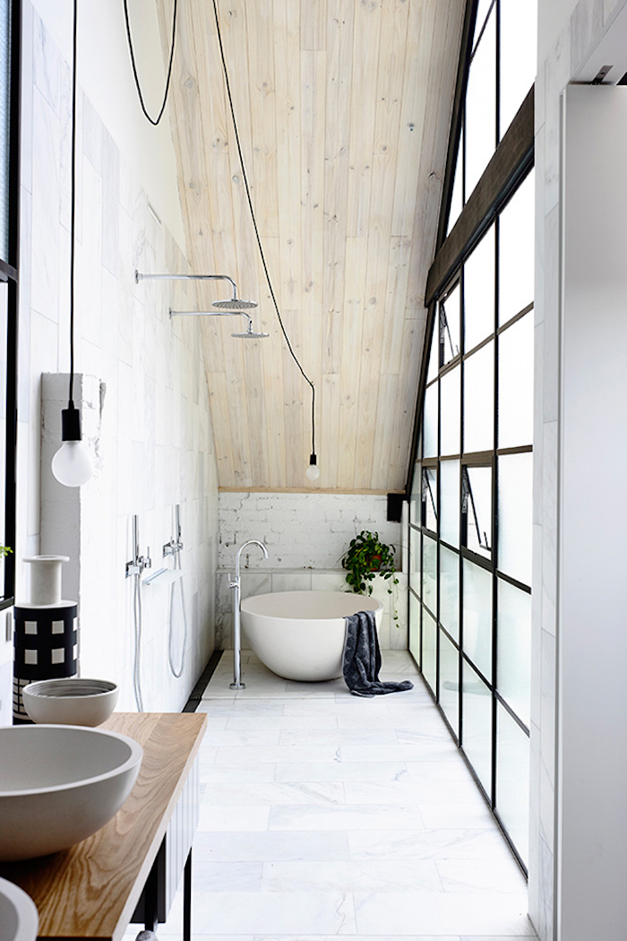salle de bain en longueur étroite aménagée sous les combles style loft scandinave avec baie vitrée industriel métal baignoire ronde ilot toit en bois et vasques rondes bol sur sol carrelage marbré blanc