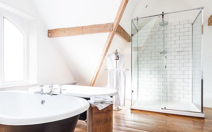 salle de bain à la scandinave avec déco suédoise avec sol en parquet et poutres apparentes en bois avec double baignoire ilot marron design et douche vitrée avec murs blancs