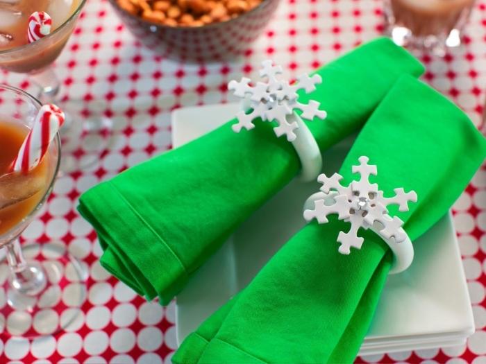 idée pliage de serviette pour noël, modèle de serviette en tissu vert décoré avec rond en plastique à design flocon de neige