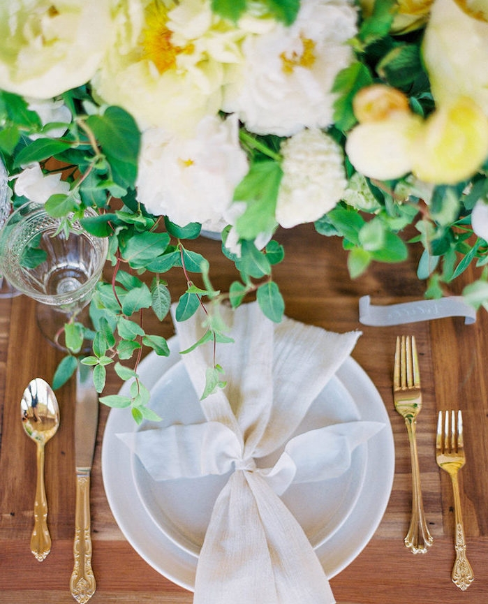 centre de table floral en fleurs blanches et jaunes sur table de bois, assiette blanche avec serviette blanche nouée d un ruban blanc, couverts dorés