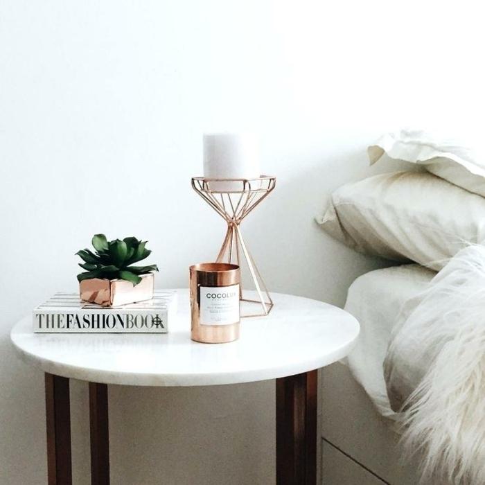 décor scandinave blanc, table ronde, grand livre blanc, mur blanc, lit au linge blanc, piètement de table bois foncé
