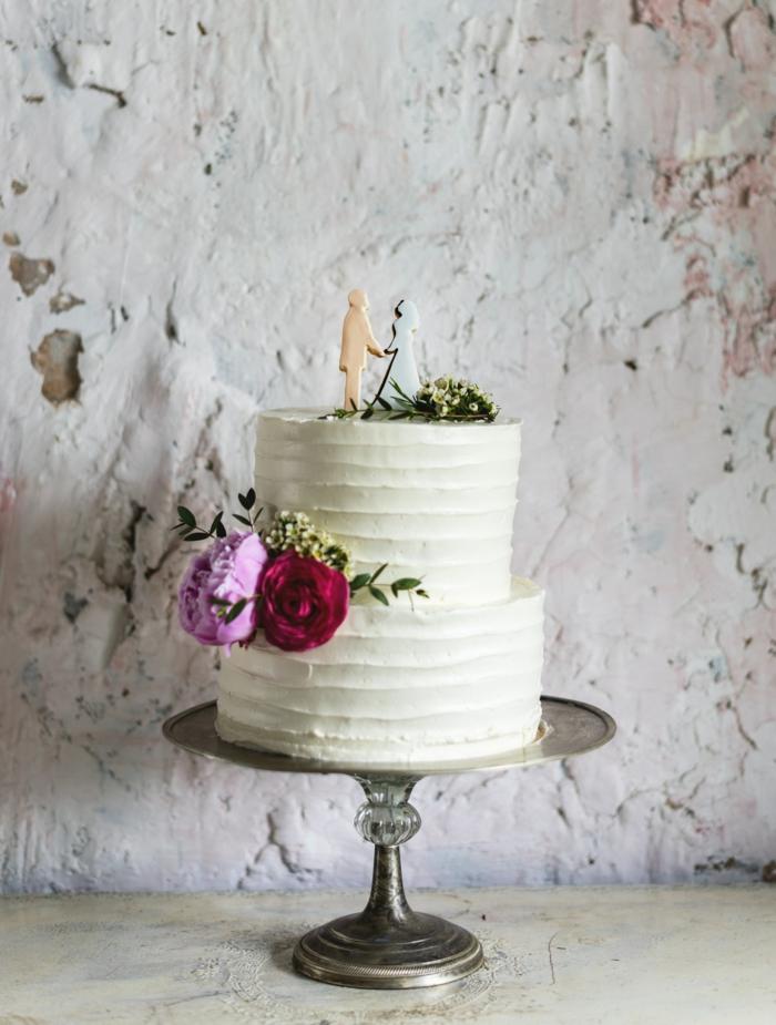Beau gateau de mariage simple en blanc avec quelques fleurs pour décoration et silhouettes des mariés pour figurines de gateau mariage