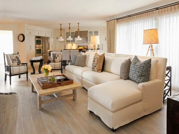 sofa d'angle crème, table basse bois, sol en bois, cuisine et salon style campagne, trois lampes suspendues blanches