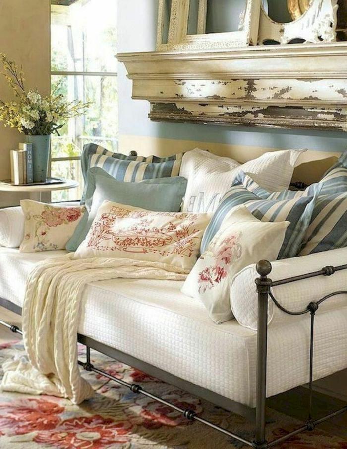 sofa blanc, tapis persan, coussins rayés, plaid tricoté couleur crème, mur bleu, vases, cadres vieillis
