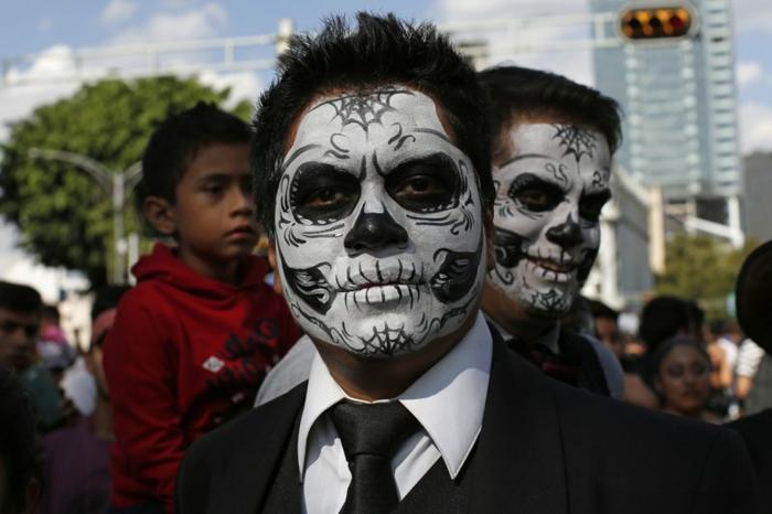 maquillage et déguisement halloween en noir et blanc, crânes apparents dessinés sur les visages