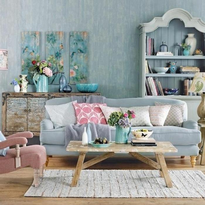 table en bois brut, fauteuil rose, table basse en bois brut, étagères bleues, commode vieillie