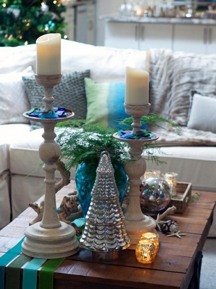 deux grandes bougies et bougeoirs hauts, decoration de table de noel, sapin couleur métalisée, bois flotté, pommes de pin, sofa, sapin de noel