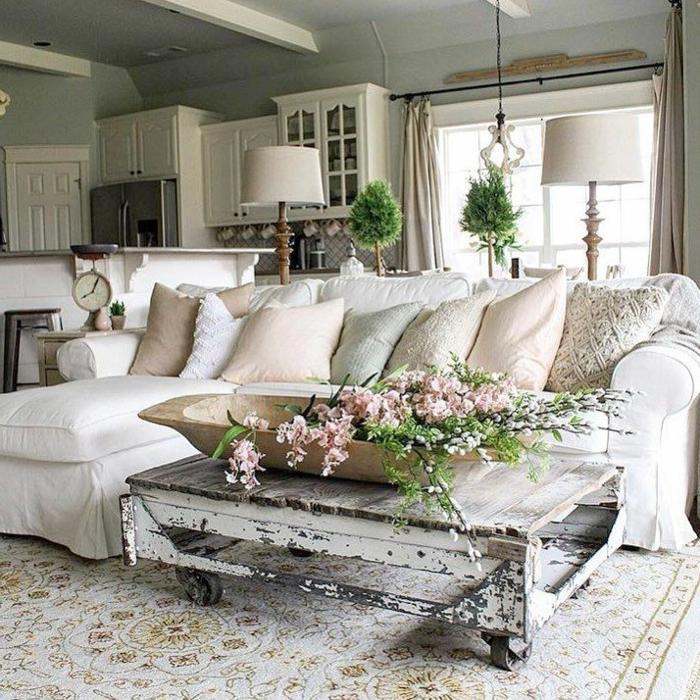 table basse en palettes patine vieillie, coussins beiges, sofa d'angle blanc, lampes abat-jour, tapis persan couleur crème, salon et cuisine