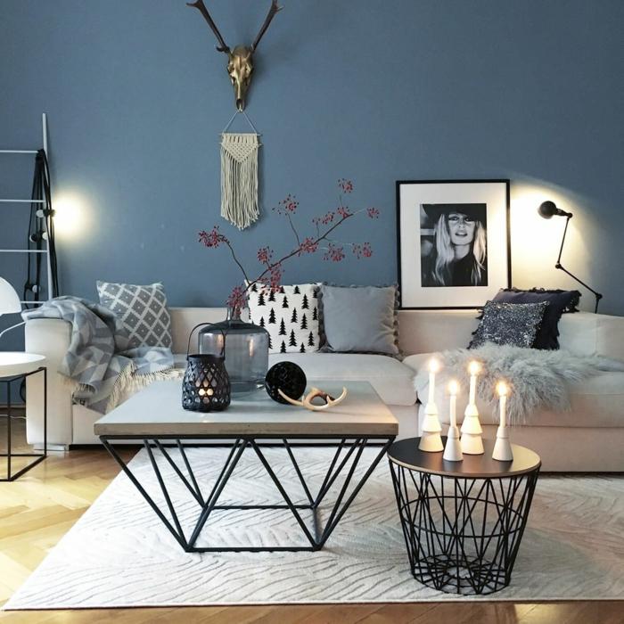 salon moderne extraordinaire, table basse design industriel, table basse ronde, bougies allumées, mur bleu, portrait en blanc et gris, déco tenture murale