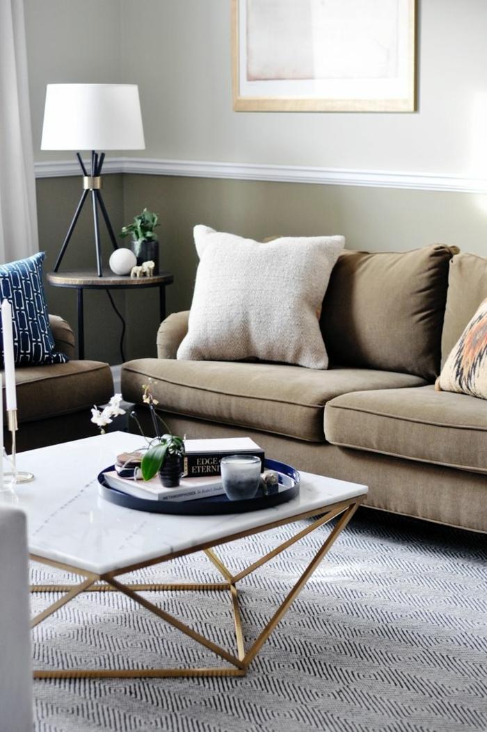 table basse design, marbre et piétement doré, sofa beige vintage, coussins déco, lampe tripode, plateau rond noir