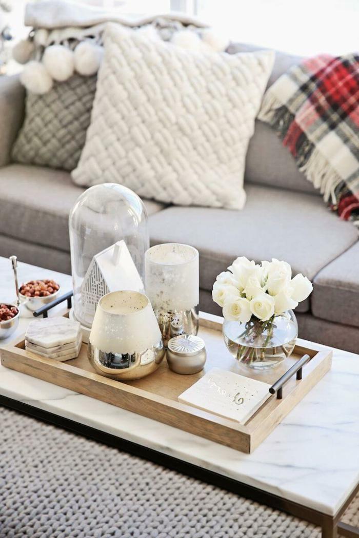 canapé gris clair, plateau en bois, vases en verre et métal argenté, coussins décoratifs, plaid carré