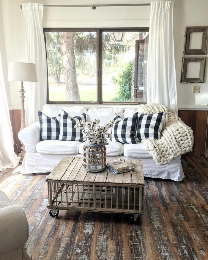 sofa blanc, table basse, rideaux blancs, coussins carreaux noirs et blancs, plaid au tricot blanc, sol en bois