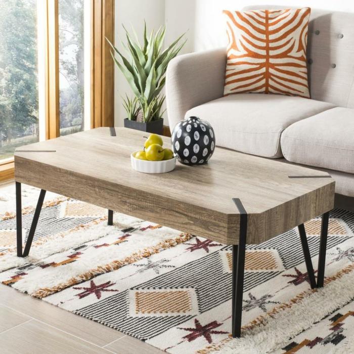 table basse en bois et fer, tapis beige aux motifs graphiques, boule décorative, plante verte, coussin motif animal
