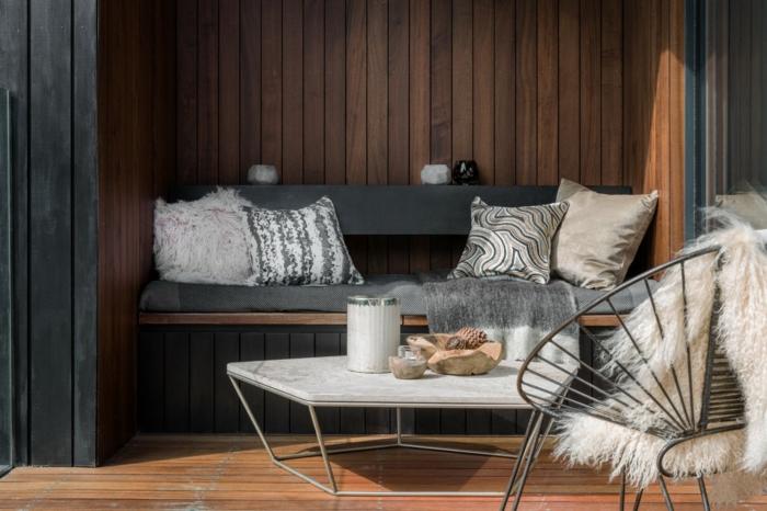 table basse marbre et fer, chaise papasan, fourrure blanche, banquette suspendue, coussins, lambris mural en bois