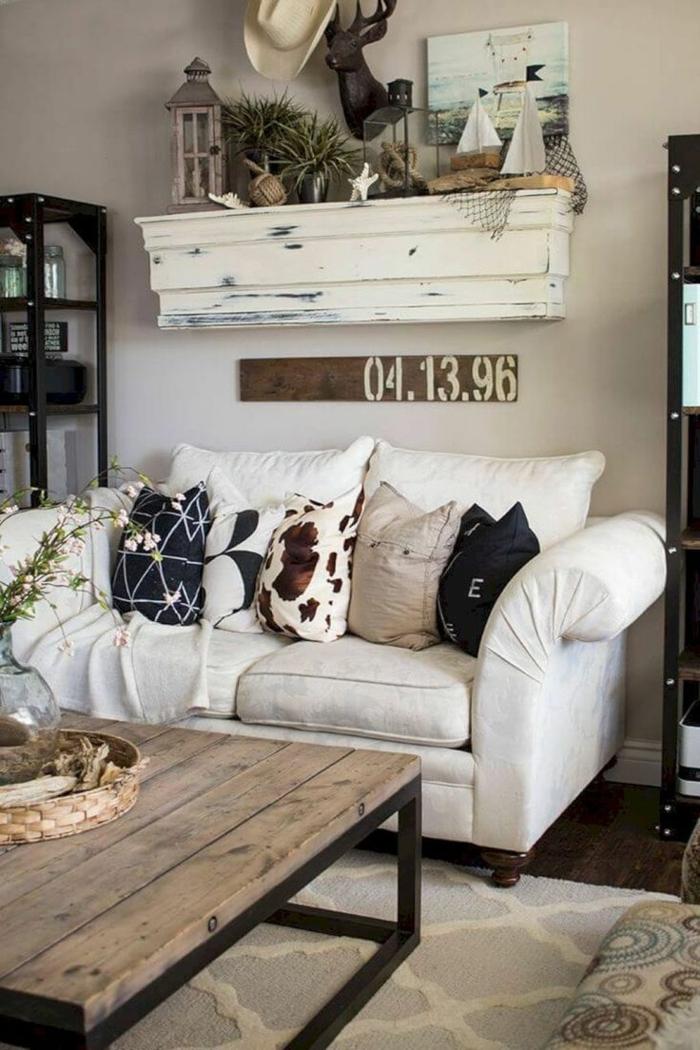 table basse industrielle, coussins déco, étagère blanche, lanterne, statuette cerf, pots de fleur, tapis shabby