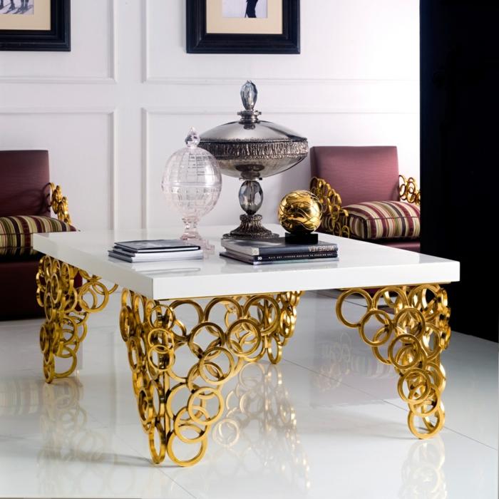 salon de luxe, piétement doré, plateau blanc, décoration avec bonbonnière en cristal, tas de magazines, fauteuils vintage
