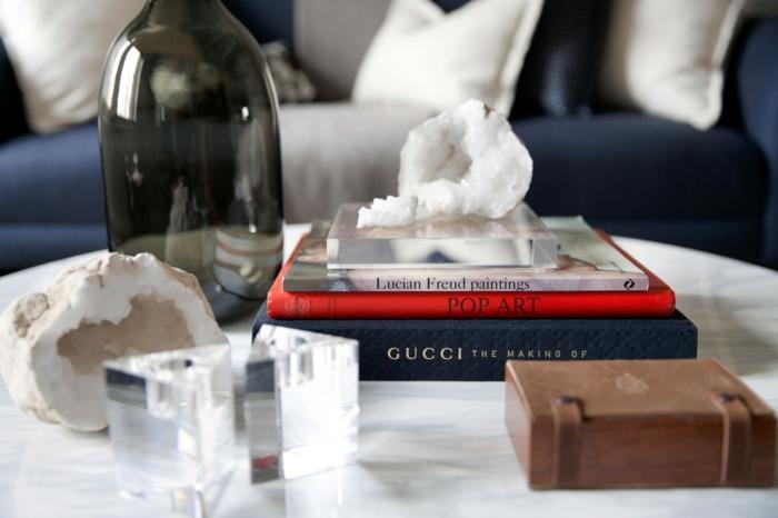 vases en verre, tas de livres, petite boîte, grand récipient en verre noir, minéraux blancs, sofa bleu