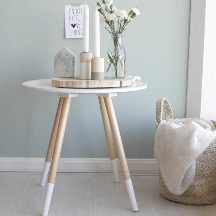 petite table ronde design scandinave, bougeoirs scandinaves et bougies blanches, bouteille de verre avec oeillets, grand panier rustique