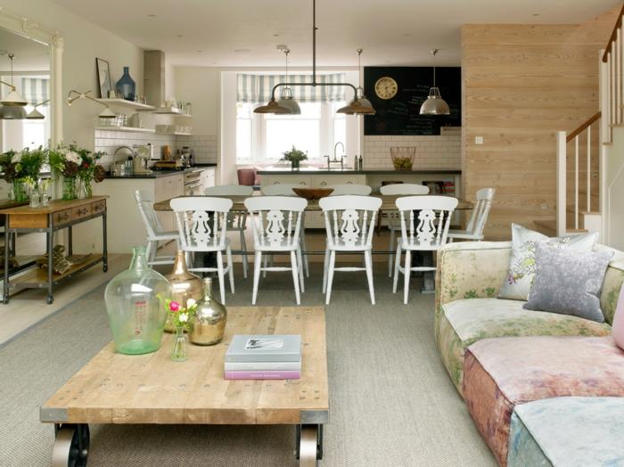 table basse industrielle, grand sofa en peluche, table de repas et chaises vintages, bureau industriel avec bouquets de fleurs