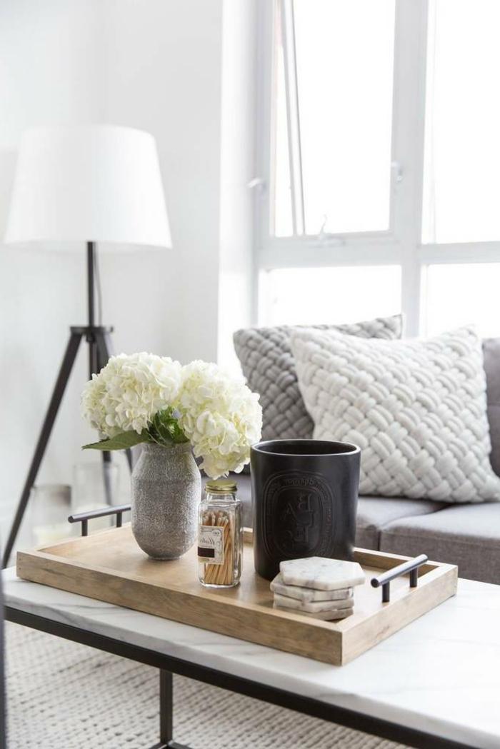 table basse en marbre, plateau en bois, vase avec hortenzias, coussins gris, sofa gris, tapis fibre naturel