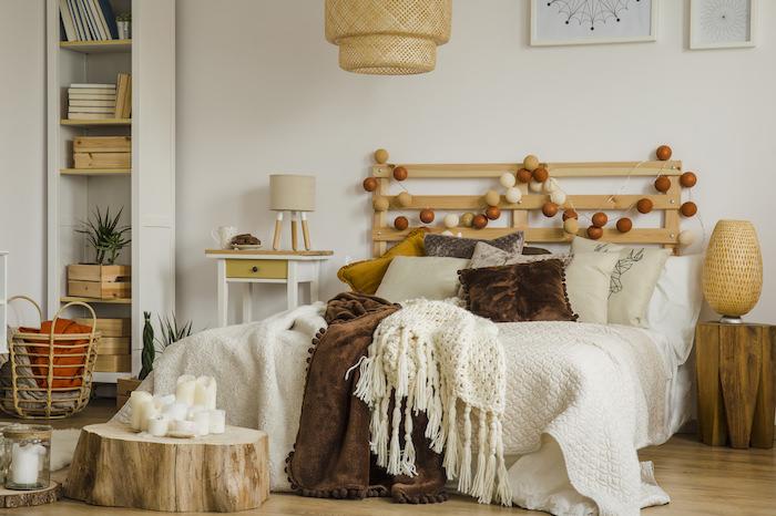 tete de lit en palette recyclée décorée de guirlande lumineuse, linge e lit en multiples plaids, parures, coussins, deco bougies, rondin de bois, parquet clair
