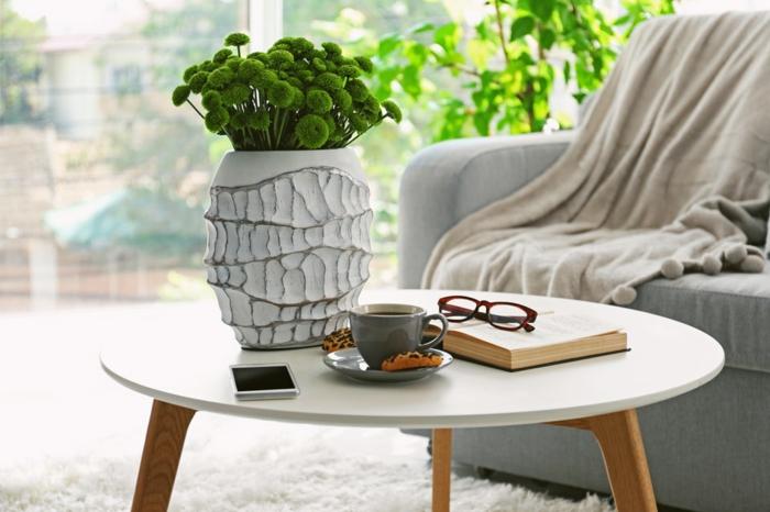 table basse scandinave, vase blanc avec fleurs vertes, livre et lunettes, tasse à café, grande plante verte, sofa gris, tapis fourrure