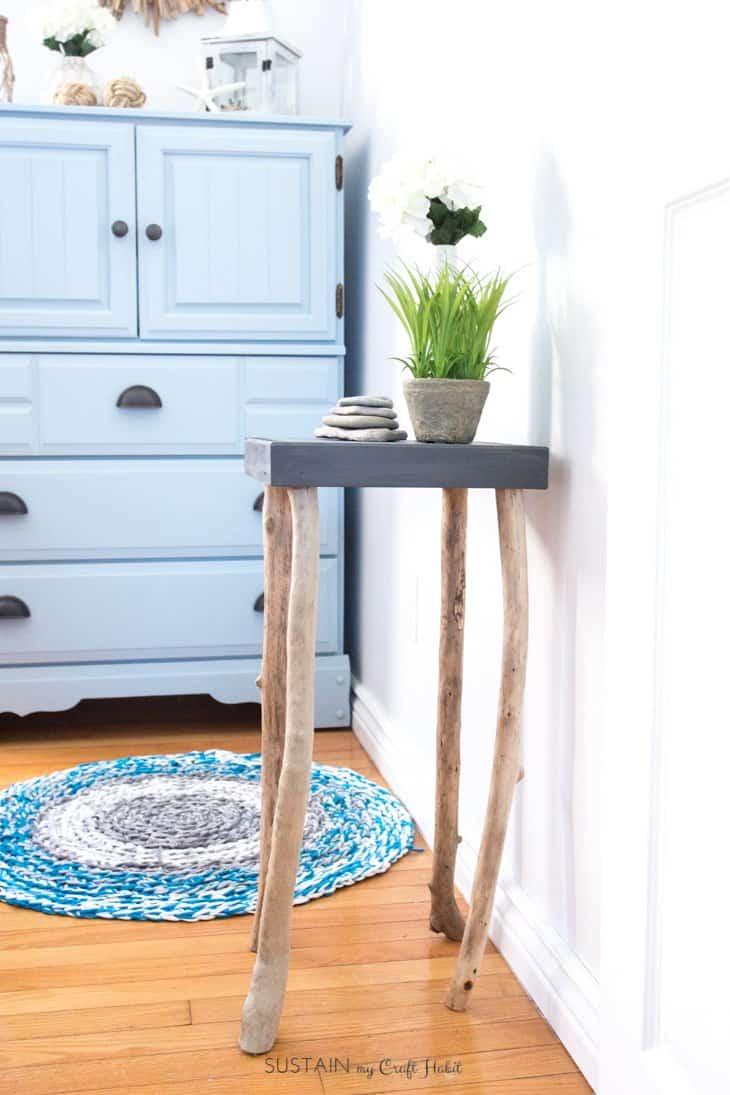 pieds de table en poteaux de bois brut taillé, plateau carré gris, table de nuit adossé à un mur style zen