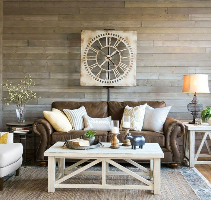 table basse blanche, tapis de jute, coussins clairs, horloge murale, sofa marron, fauteuil gris clair, lampe de table