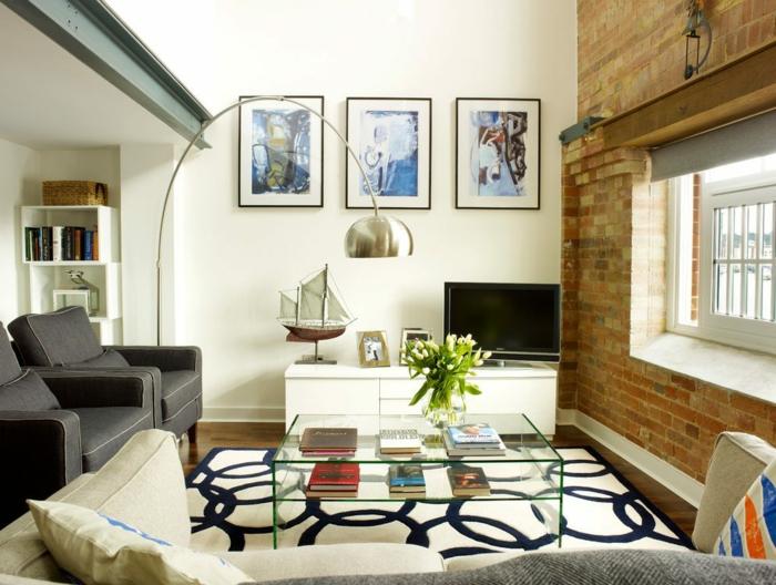 tapis blanc aux motifs noirs, table basse en verre, tas de livres, vase avec tulipes blanches, lampadaire arc, fauteuils gris