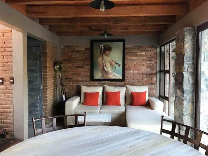 grande table ronde, chaises métalliques, sofa avec coussins rouges, portrait encadré, plafond en bois