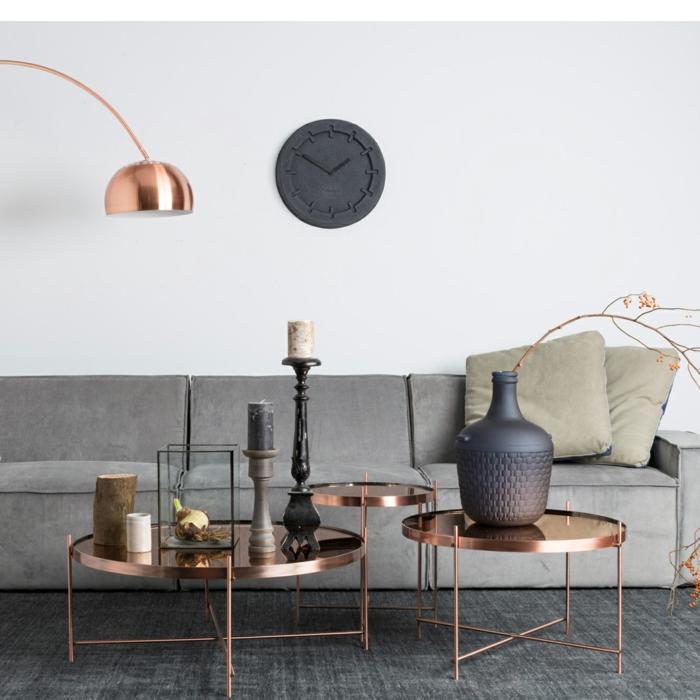 tapis gris, tables basses cuivrées, grand vase gris avec un rameau, bougeoirs élégants, lampe de sol cuivrée