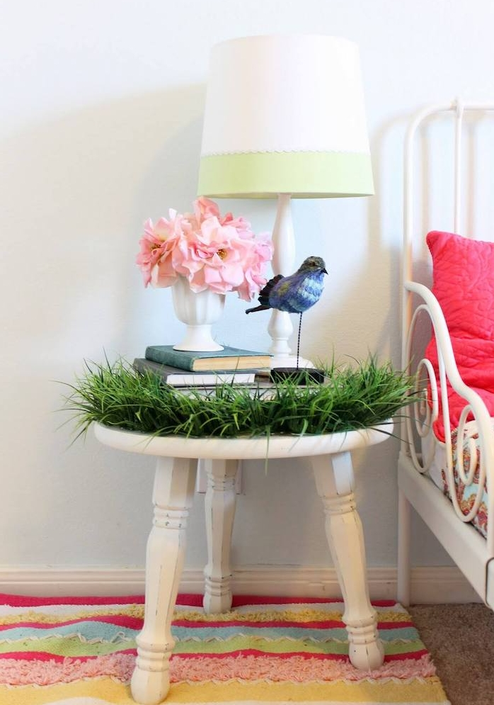 tabouret blanc pour votre table de service nuit avec herbe artificielle, bouquins, bouquet de fleurs, tapis à rayures, lit metallique blanc