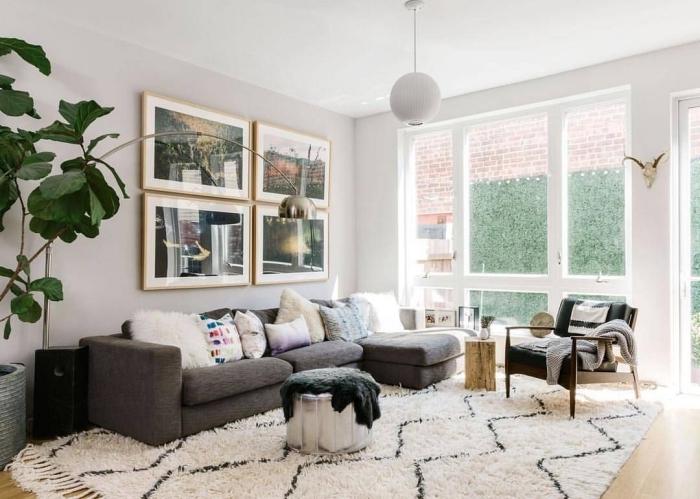 deco salon scandinave avec grand canapé d'angle gris pimpé de coussins dépareillés et un tapis cocooning de style bohème chic qui rendent l'ambiance douce et chaleureuse