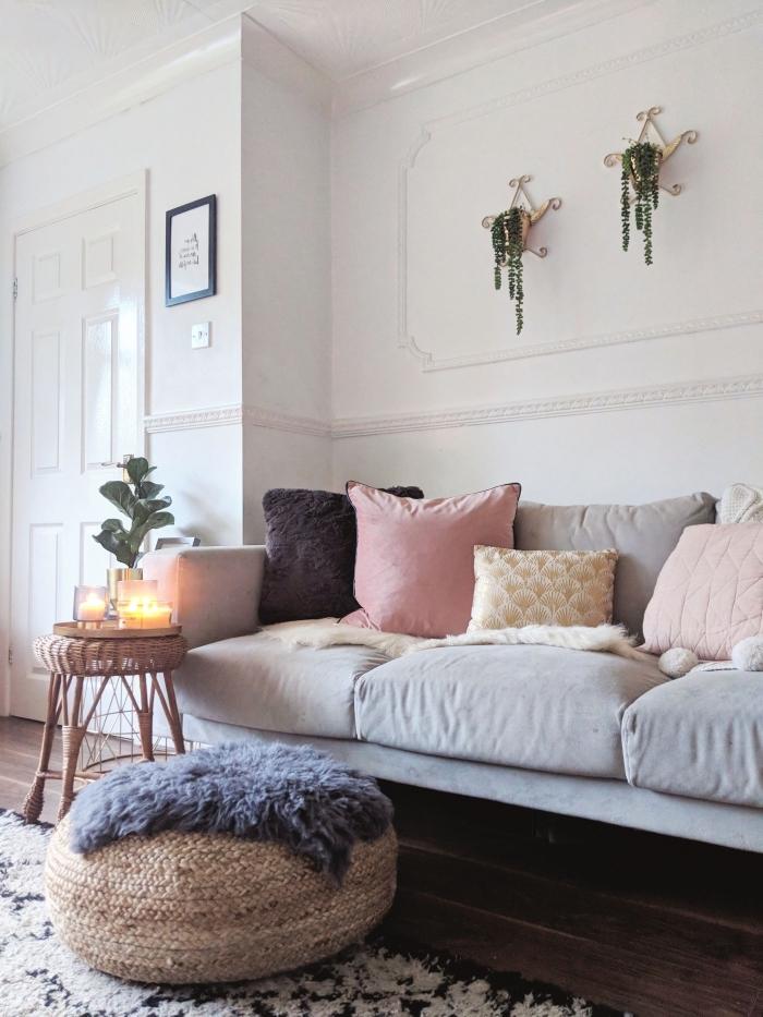 image cocooning d'un intérieur hygge danois, coin cocooning dans le salon avec un canapé gris recouvert de coussins décoratifs, un pouf en jute et une table d'appointe déco