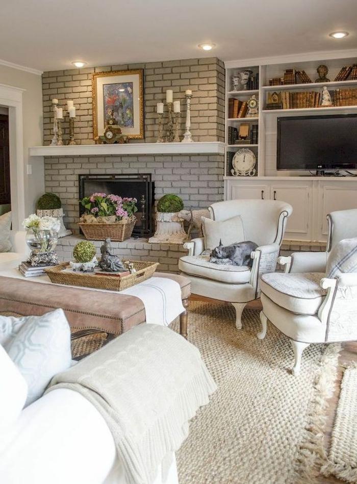 deux fauteuils blancs, ottoman taupe, sofa gris clair, tapis en jute, étagère blanche, bougeoirs anciens, meuble bibliothèque blanc