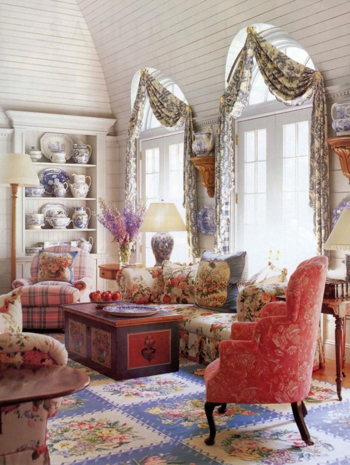 fauteuil rouge, table vintage avec rangement, tapis patchwork, grandes fenêtres arquées, étagère ouverte, fauteuil carré en rose