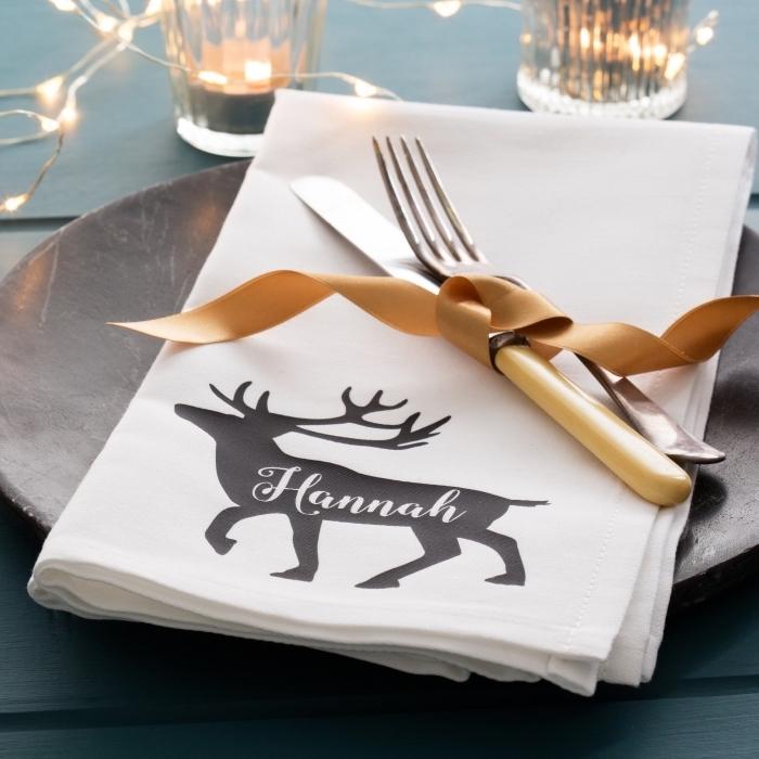 comment arranger une table Noel, déco de table pour fête, modèle de serviette en tissu blanc avec imprimé noel, pliage serviette noel