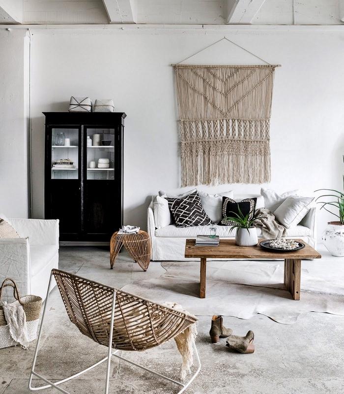 ambiance authentique et ethnique chic dans ce salon en tons neutres, avec canapé blanc surmonté d'une tapisserie macramé