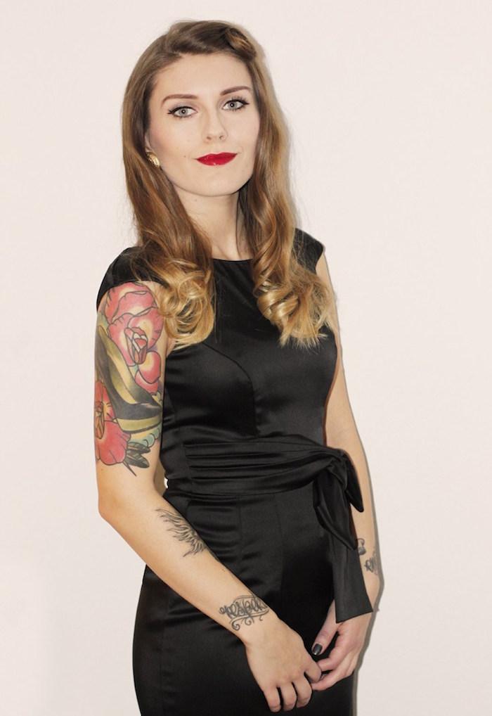 tenue de soirée femme avec robe noire sur theme pin up des années 50 avec maquillage retro et tatouage sur le bras et poinget