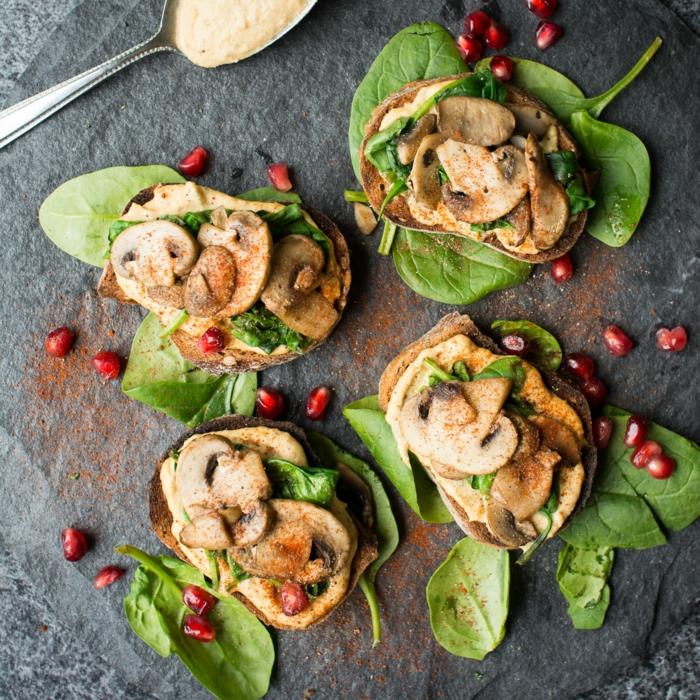 champignons tranchés sur tranches de pin, feuilles d'épinards, graines de grenade, plateau ardoise