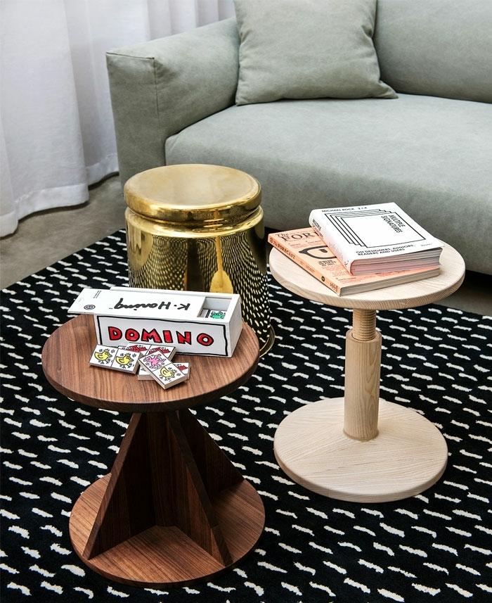 déco originale de salle de séjour, deux petites tables en bois, petite table dorée, tapis noir aux traits blancs, grand sofa