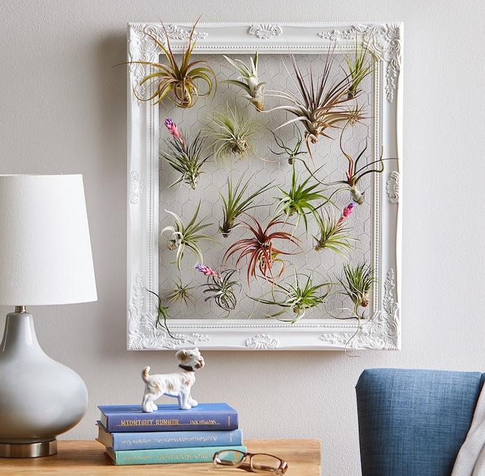 tableau vegetal décoratif avec des fleurs des airs accrochées sur un grillage encadré sur mur blanc, pile de livres, figurine chien, plante d intérieur originale