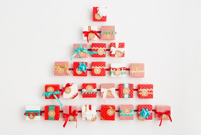 petits cadeaux en boîtes cadeaux miniatures couleur rouge et blanc sur une bande de ruban rouge en forme de sapin de noel sur mur blanc, calendrier de l avent personnalisé