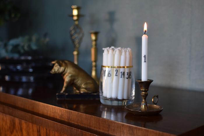idée originale et simple de calendrier de l avent adulte en bougies blanches numérotées à chiffres en noirs sur commode vintage