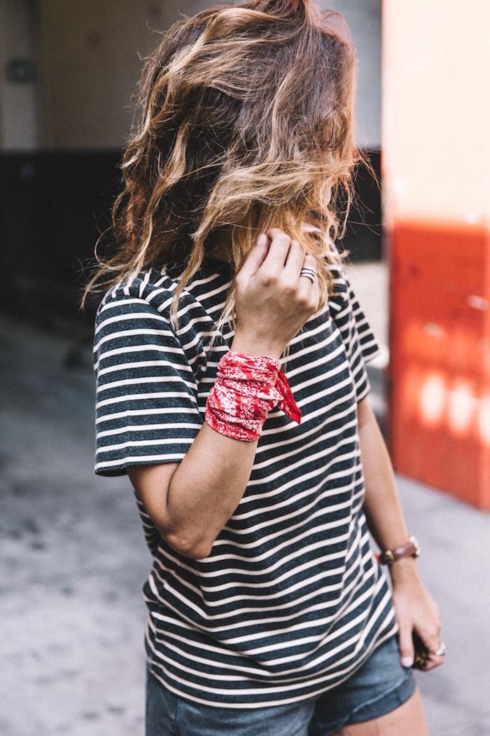 femme avec tee shirt rayé style marinière avec foulard rouge style bandana attaché au poignet comme un bracelet
