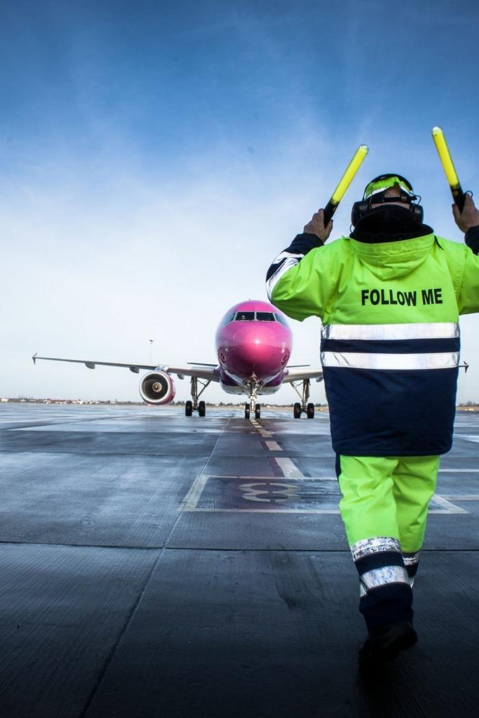 un homme qui travaille à l'aéroport en son vêtement de travail haute visibilité, veste aux réflecteurs avec script