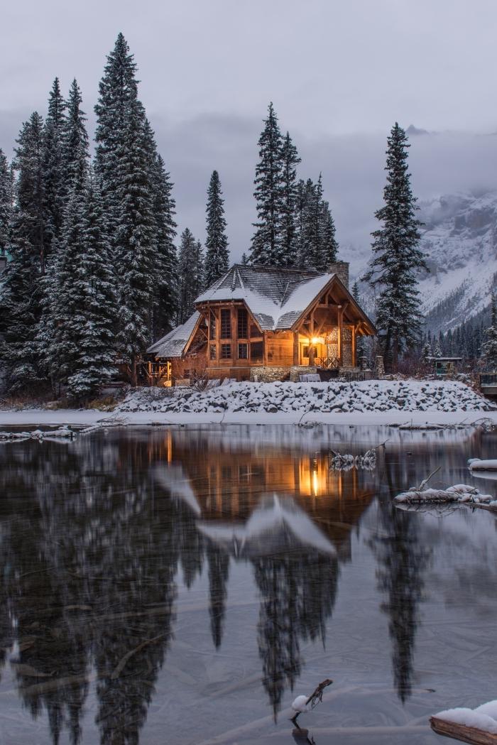 magnifique paysage hiver dans une forêt enneigée, photo de maison en bois au bord d'un lac dans les montagnes
