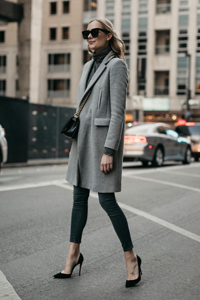 femme blonde dans la rue, jeans skinny, escarpins noirs, pull col montant, sac noir
