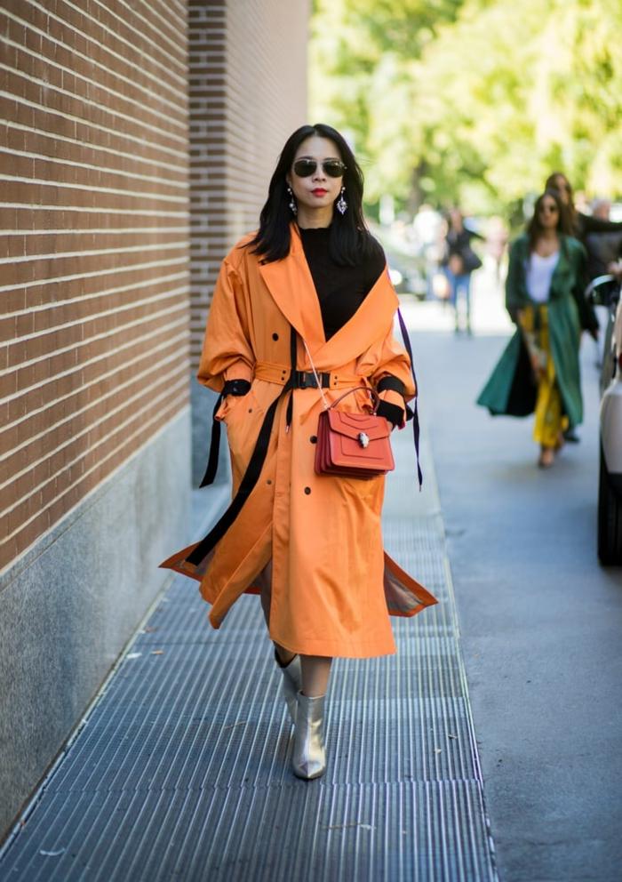 trench orange, bottes couleur métal argenté, sac rouge avec bandoulière chaîne, pull noir