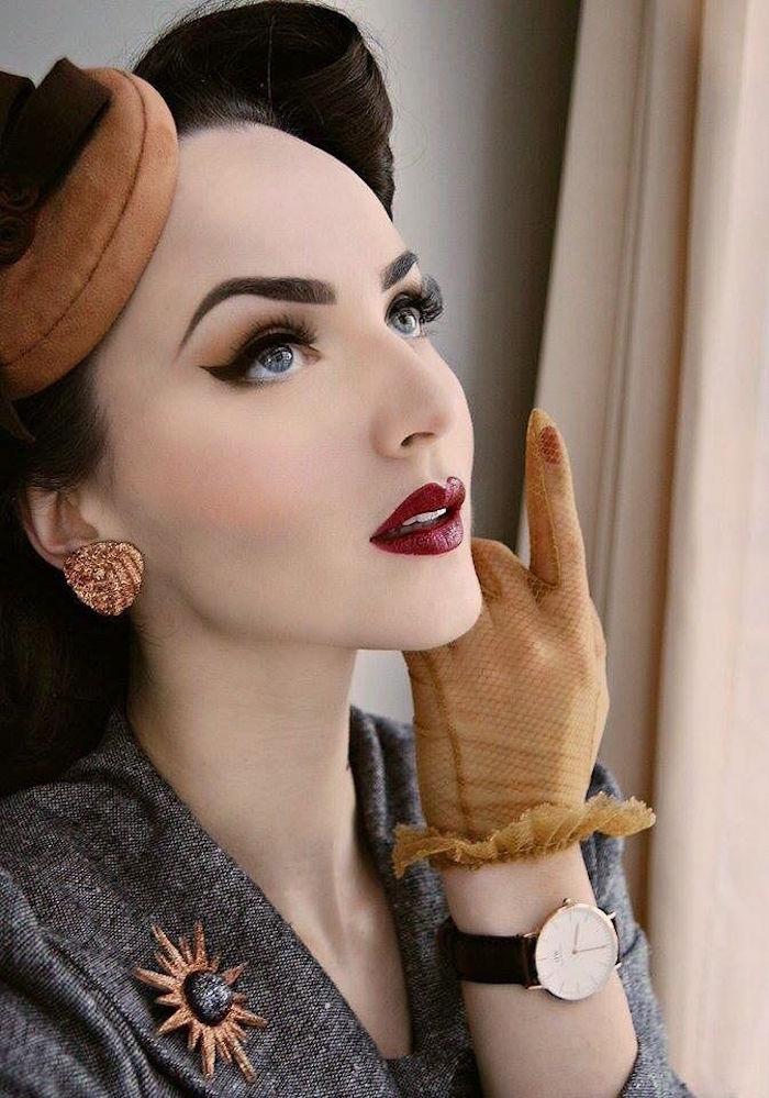 tenue classe dame des années 50 avec accessoires gants et veste grise avec maquillage appuyé rétro pin up sur fond de teint blanc et coiffure enroulée victory rolls